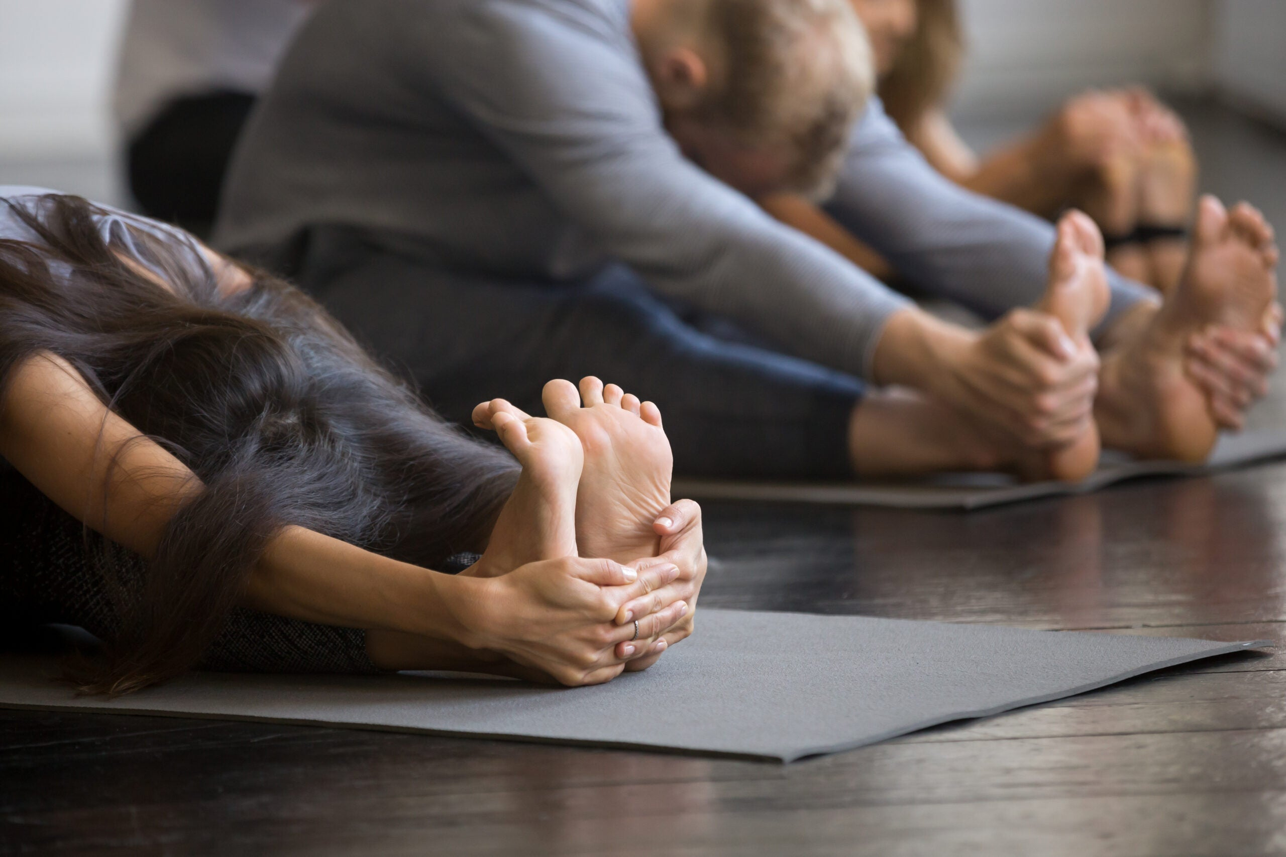 Yoga students hold their stretches in seated forward folds