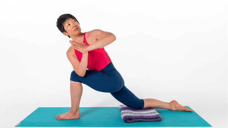 A woman demonstrates a variation of Revolved Side Angle with her back knee down