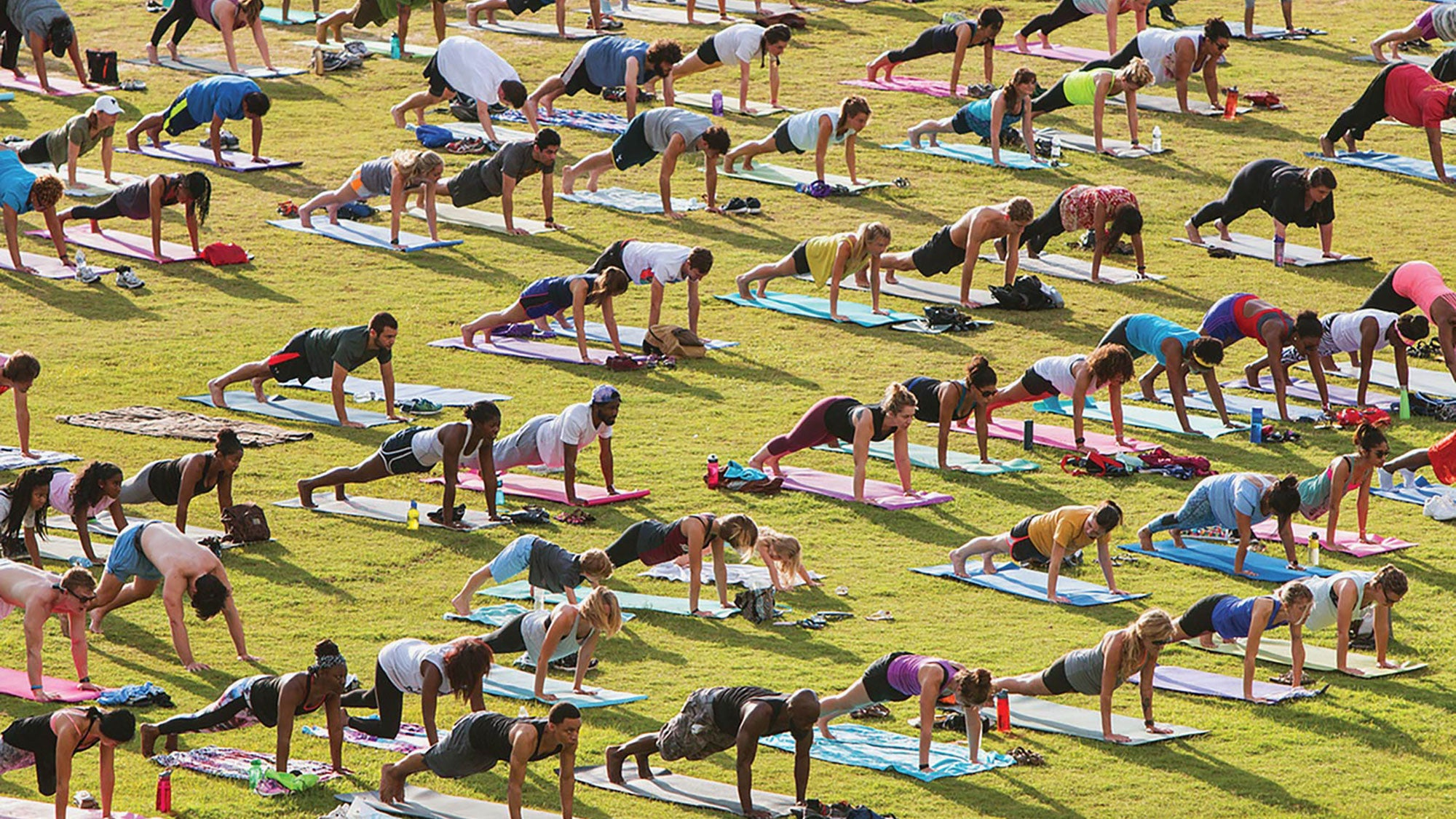 Lots of people doing yoga in a field of grass