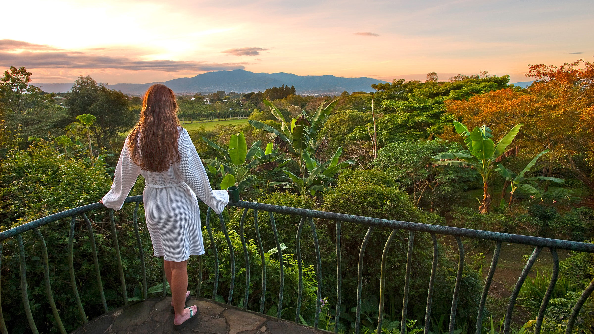 Woman stands on balcony overlooking Costa Rica at sunset