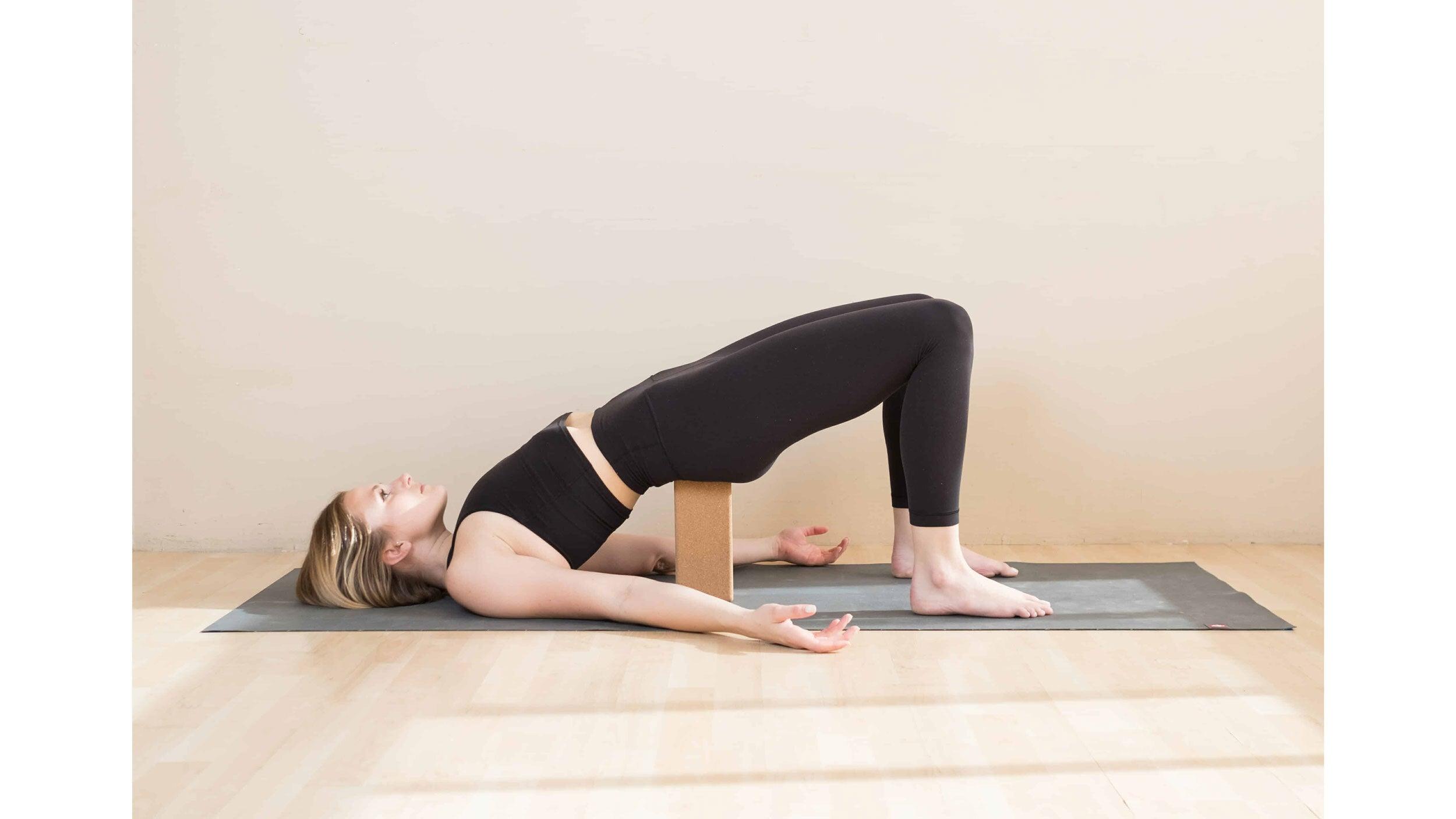 A woman performs Setu Bandha Sarvangasana, variations (Bridge Pose) in yoga