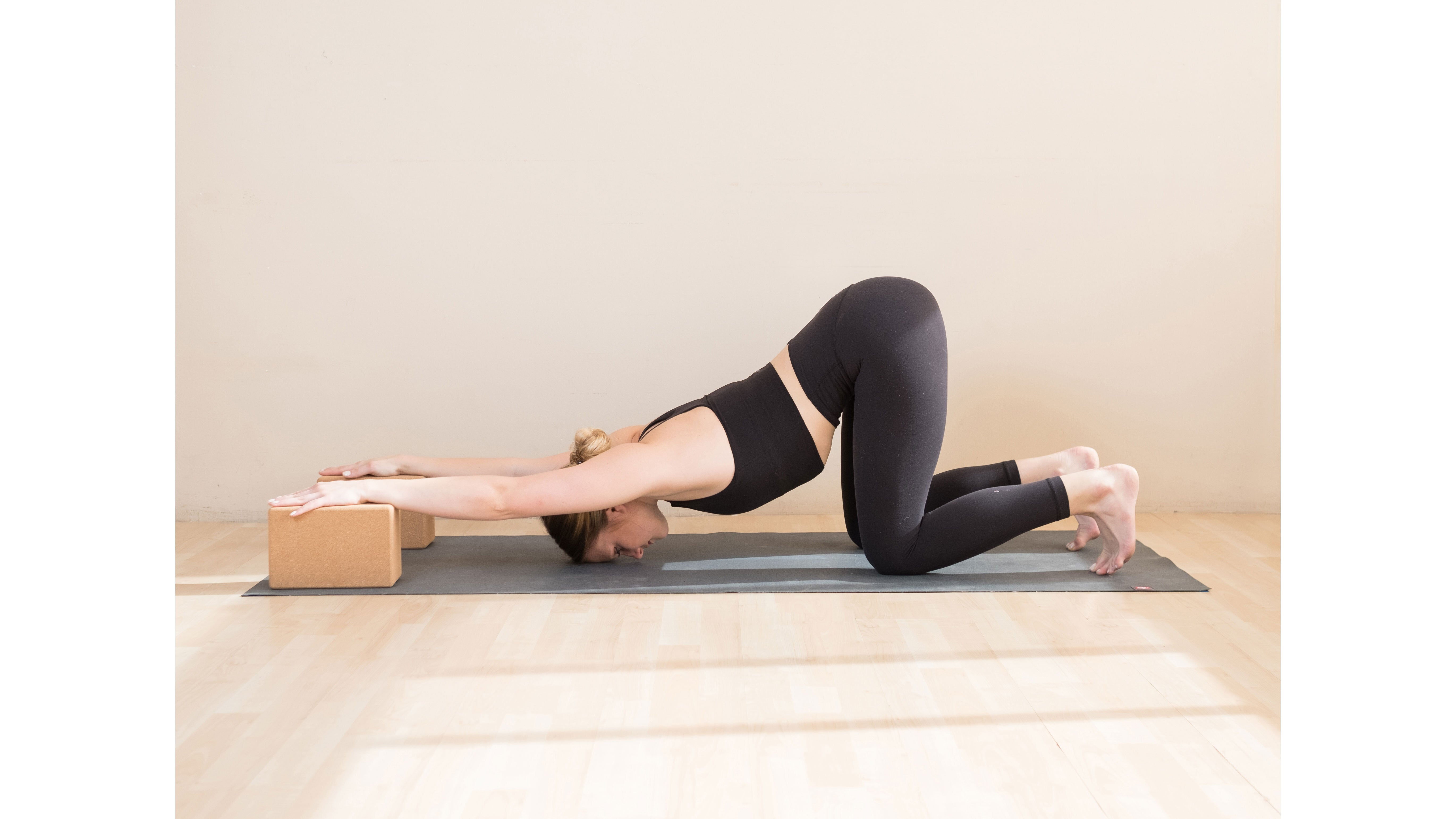 A woman performs Uttana Shishosana (Extended Puppy Pose) variation with blocks