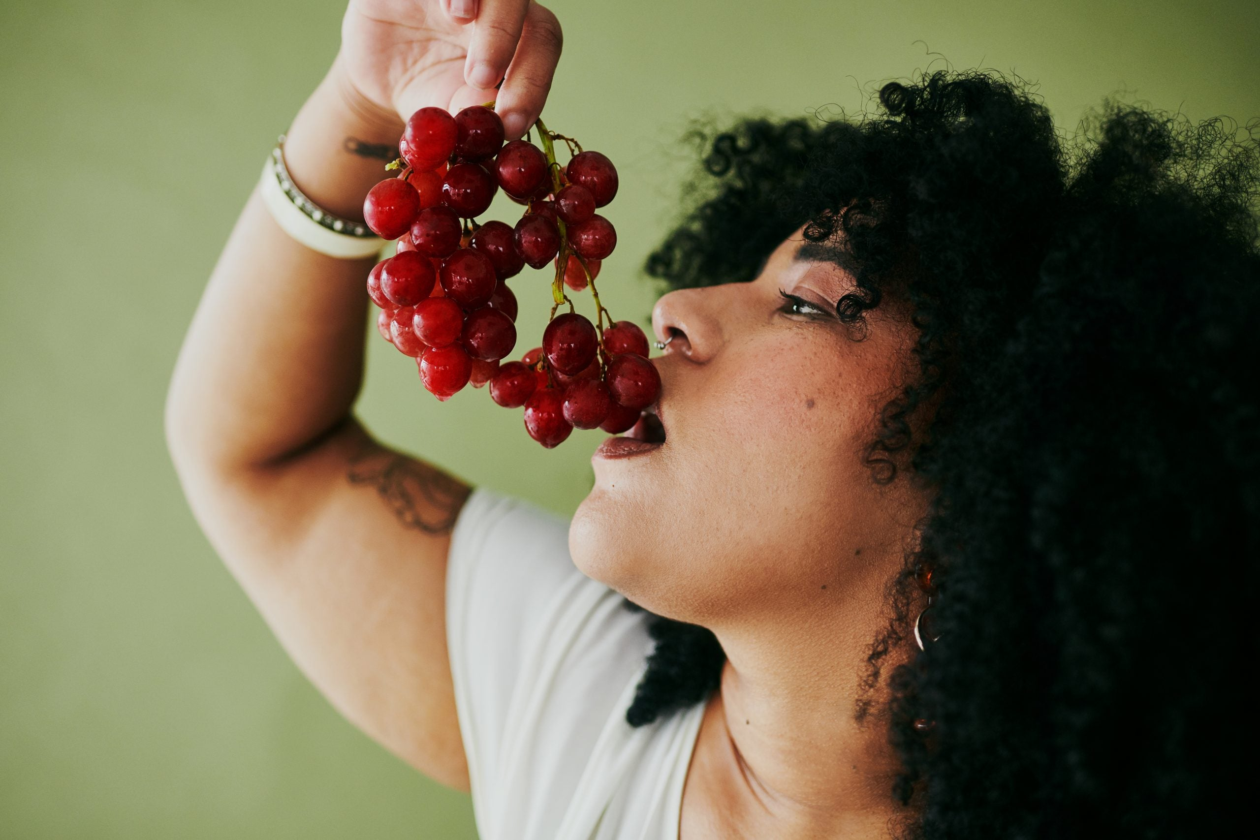 Woman with curly, black hair eating a bunch of red grapes. White shirt, green background