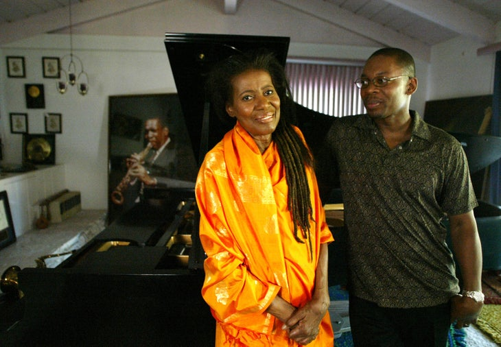 """Alice Coltrane and her son Ravi in front of a photograph of John Coltrane and the piano he offered to Alice in 1964. Alice and Ravi Coltrane just released an album together entitled """"Translinear Light"""". (Photo by J. Emilio Flores/Corbis via Getty Images)"""