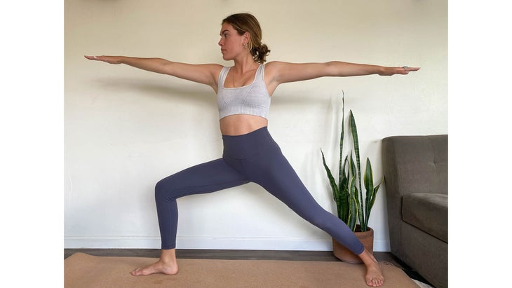 A woman demonstrates Warrior II pose in yoga