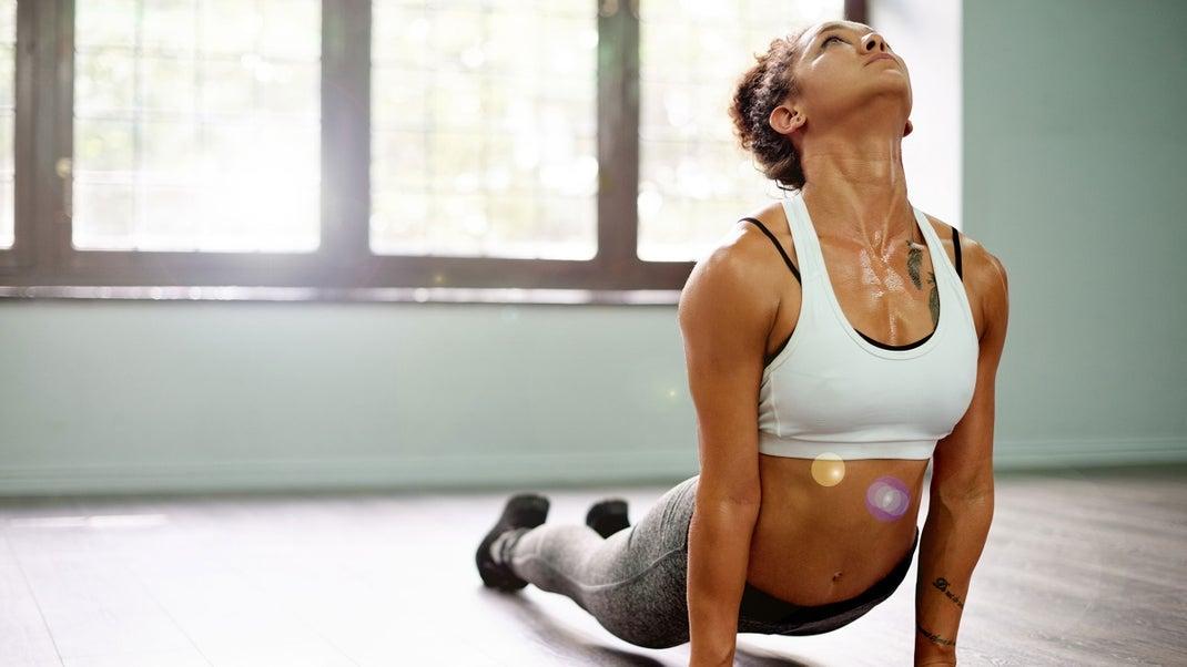 A woman sweats while demonstrating upward-facing dog in yoga