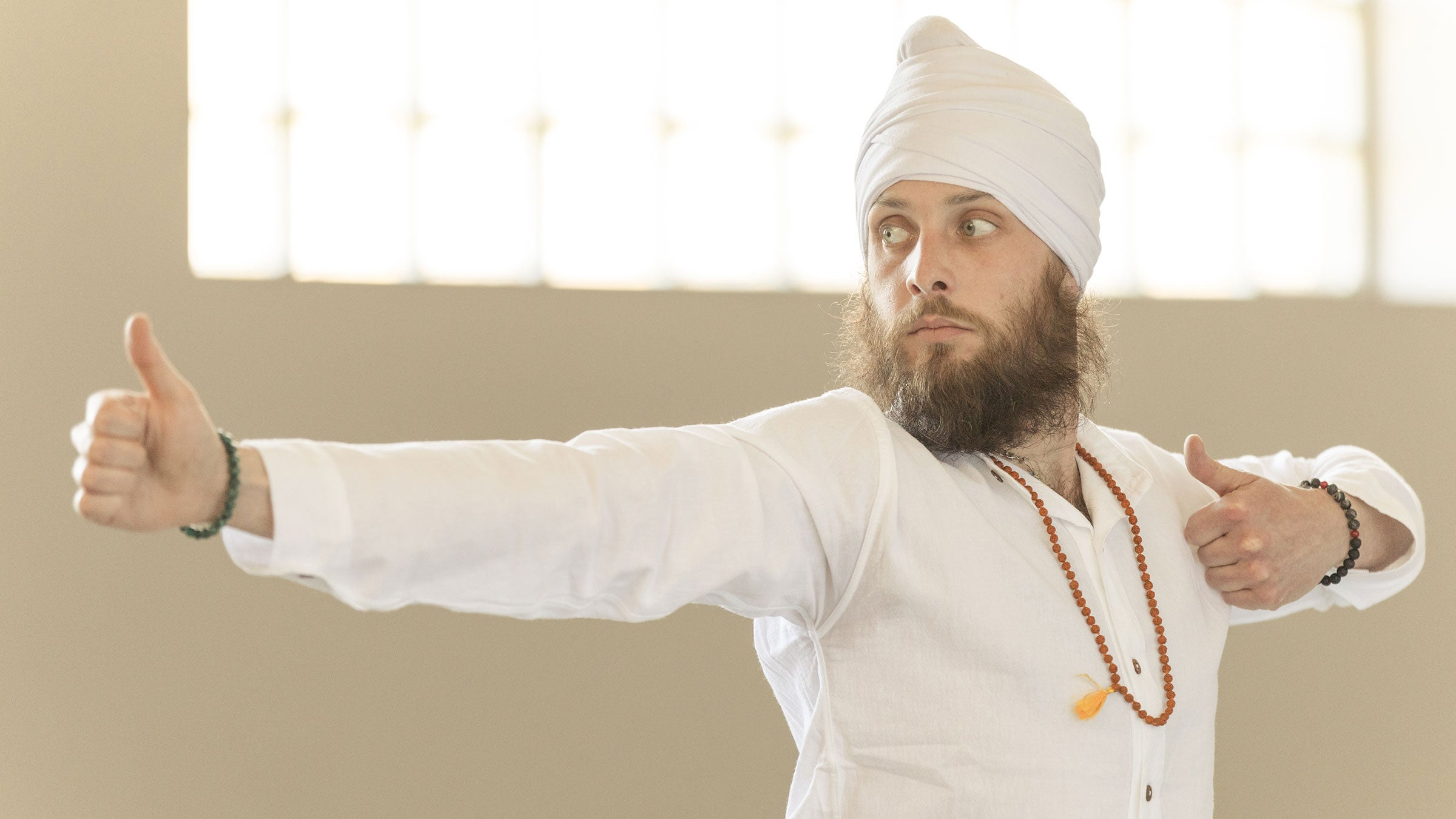 A man practices Kundalini Yoga wearing all white