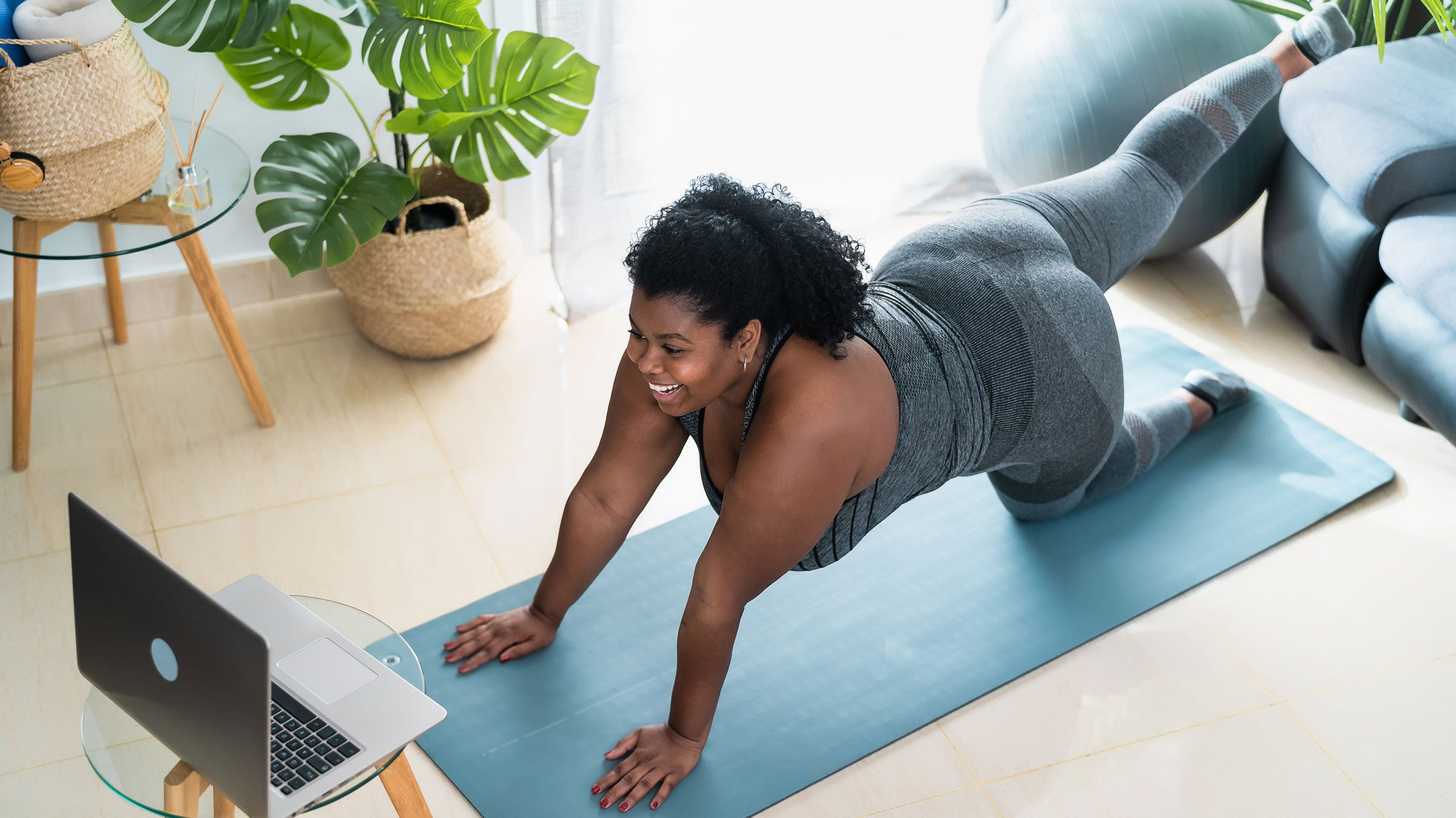 A woman pratices virtual yoga at home in her living room
