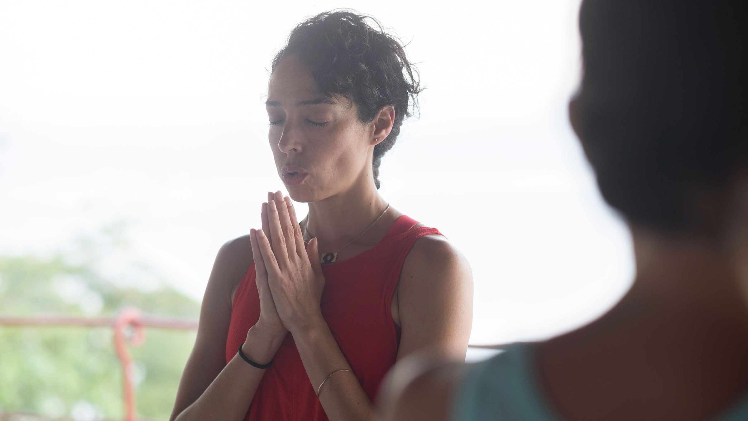 A woman breathes out softly through her mouth during a yoga class