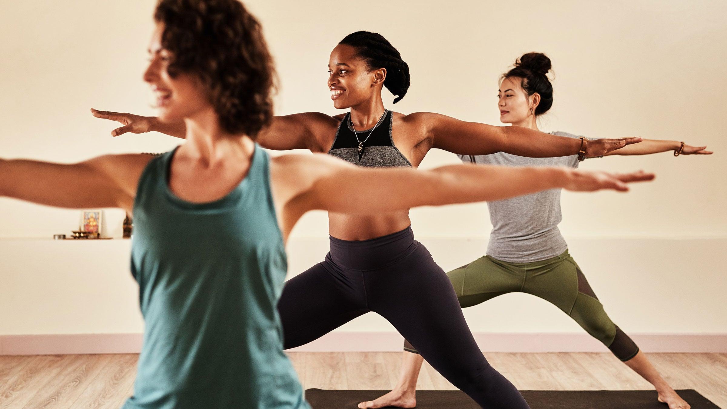 Women demonstrate Warrior II in yoga class