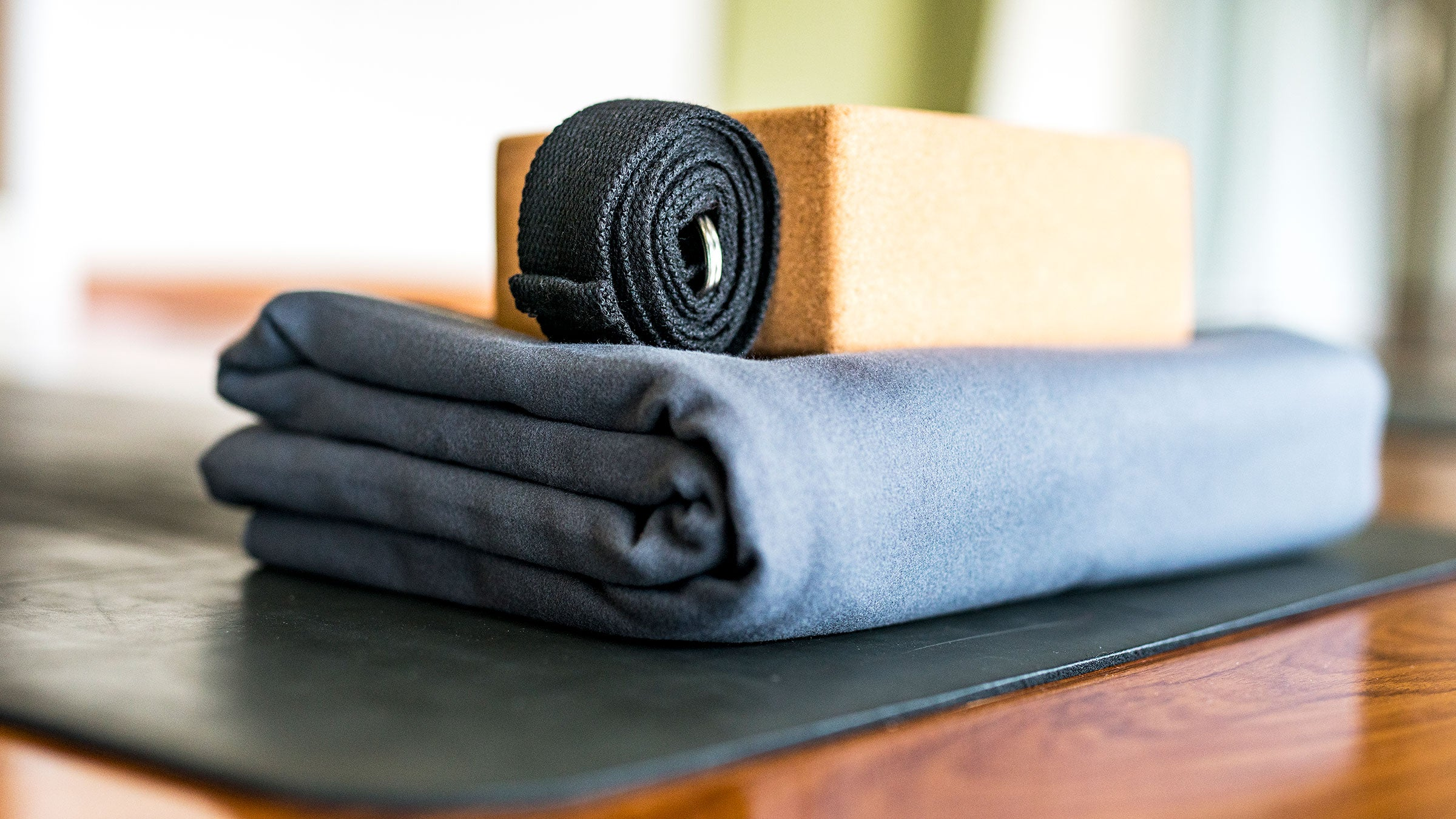 A yoga mat, block, strap, and blanket are pictured in a studio