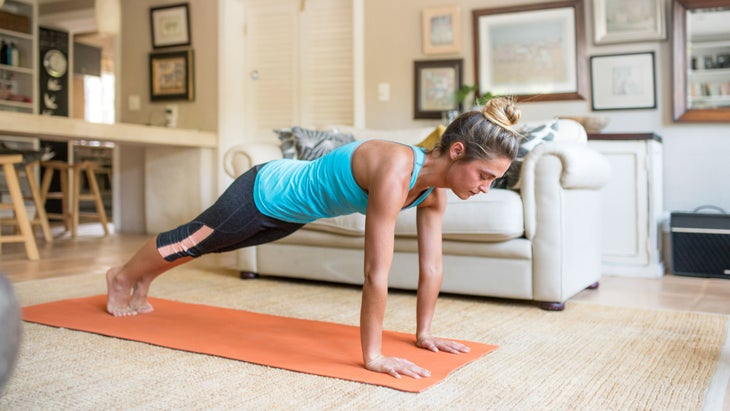 Girl does Plank Pose at home in her living room