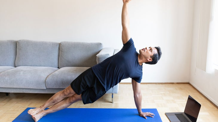 Man practice side plank at home