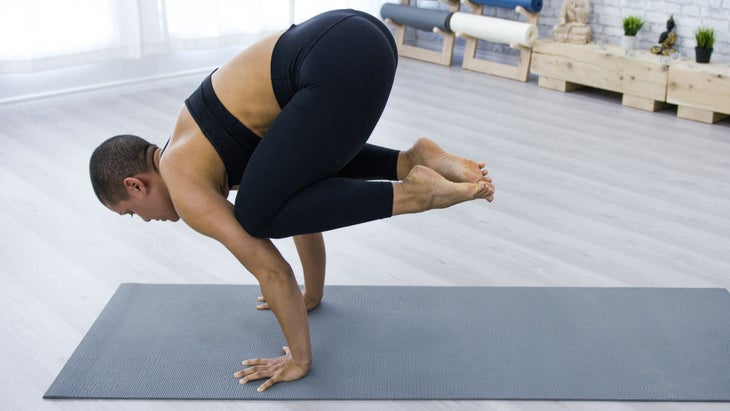 Woman practices Crow Pose in her home